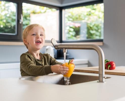 kindje wast de groenten onder de kraan